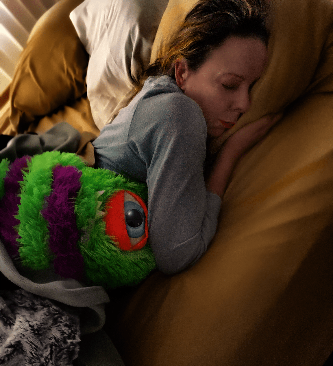 Young woman curled up with stuffed alien toy