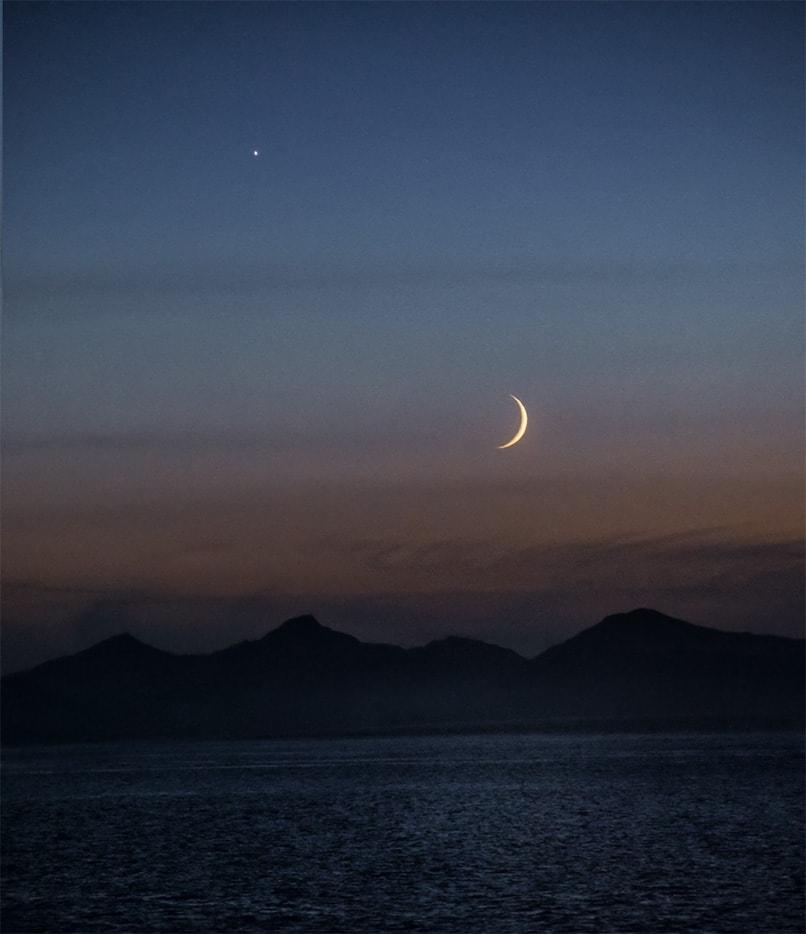 Alaskan crescent moonset on water taken from ship